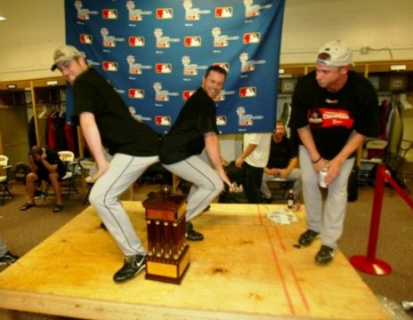 Happy days: Chad Qualls and Brad Lidge get down with the NL trophy while Brandon Backe gets his groove on from the side.